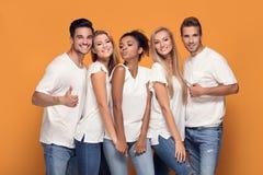Grupo de amigos bonitos que levantam junto no estúdio imagens de stock royalty free