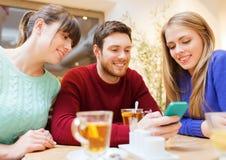 Grupo de amigos com reunião do smartphone no café imagem de stock