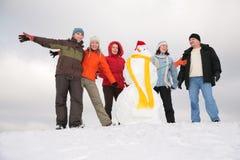 Grupo de amigos con el muñeco de nieve Fotografía de archivo libre de regalías