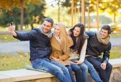 Grupo de amigos con la cámara de la foto en parque del otoño Foto de archivo