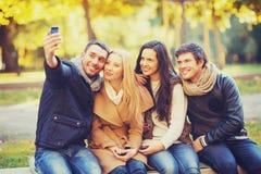 Grupo de amigos con la cámara de la foto en parque del otoño Imágenes de archivo libres de regalías