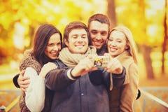 Grupo de amigos con la cámara de la foto en parque del otoño Fotografía de archivo