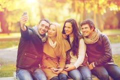 Grupo de amigos con la cámara de la foto en parque del otoño Imagenes de archivo