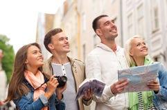 Grupo de amigos con la guía, el mapa y la cámara de la ciudad fotos de archivo libres de regalías