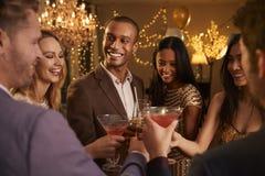 Grupo de amigos con las bebidas que disfrutan del cóctel fotografía de archivo
