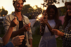Grupo de amigos con las bengalas que disfrutan del partido al aire libre Fotos de archivo libres de regalías