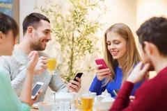 Grupo de amigos con los smartphones que se encuentran en el café Imagenes de archivo