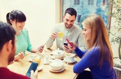 Grupo de amigos con los smartphones que se encuentran en el café Fotografía de archivo libre de regalías