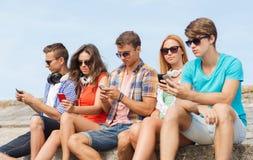 Grupo de amigos con smartphones al aire libre Foto de archivo libre de regalías