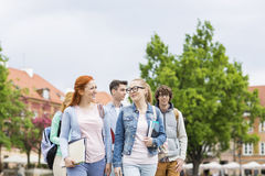 Grupo de amigos da faculdade que andam fora foto de stock royalty free