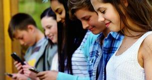 Grupo de amigos de la escuela que usan el teléfono móvil fuera de la escuela