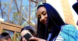 Grupo de amigos de la escuela que usan el teléfono móvil fuera de la escuela metrajes