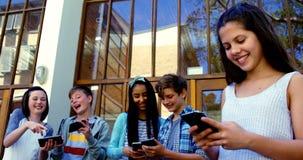 Grupo de amigos de la escuela que usan el teléfono móvil fuera de la escuela almacen de video