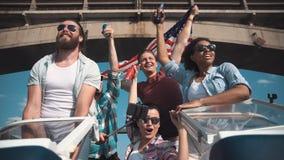 Grupo de amigos de riso cheering em uma lancha fotos de stock