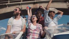 Grupo de amigos de riso cheering em uma lancha filme