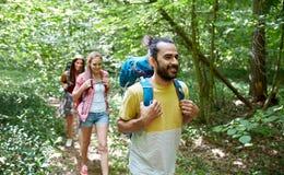 Grupo de amigos de sorriso com caminhada das trouxas Imagens de Stock