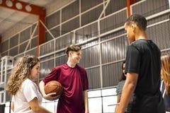 Grupo de amigos del adolescente en hablar de la cancha de básquet Foto de archivo