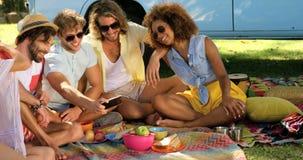 Grupo de amigos del inconformista que miran algo en smartphone almacen de video