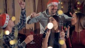 Grupo de amigos del joyfull que cantan el Karaoke que se divierte en la fiesta de Navidad 4K almacen de metraje de vídeo