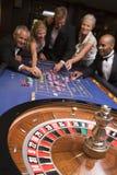 Grupo de amigos del juego en casino imágenes de archivo libres de regalías