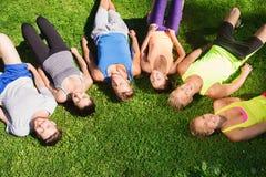 Grupo de amigos deportivos felices en círculo al aire libre Fotos de archivo libres de regalías