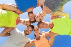 Grupo de amigos deportivos felices en círculo al aire libre Foto de archivo