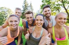 Grupo de amigos deportivos felices que muestran los pulgares para arriba Fotos de archivo libres de regalías