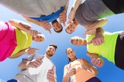 Grupo de amigos deportivos felices que muestran los pulgares para arriba Fotografía de archivo