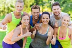Grupo de amigos deportivos felices que muestran los pulgares para arriba Imagenes de archivo