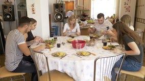 Grupo de amigos desapasibles que se sientan junto en la tabla que come un almuerzo nutritivo que charla en casa a los demonios ca almacen de video
