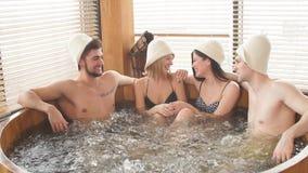 Grupo de amigos diversos caucásicos que gozan del Jacuzzi en balneario del hotel almacen de metraje de vídeo