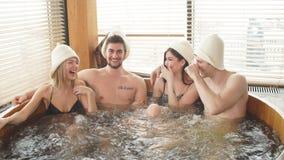 Grupo de amigos diversos caucásicos que gozan del Jacuzzi en balneario del hotel almacen de video