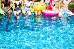 Grupo de amigos diversos que disfrutan de tiempo de verano por la piscina con i fotos de archivo