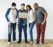 Grupo de amigos diversos que usan el ordenador portátil junto fotos de archivo libres de regalías