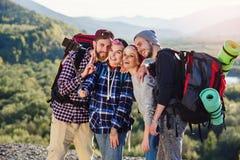 Grupo de amigos do moderno que usam o telefone esperto a fazer o selfie no fundo da montanha durante o dia ensolarado Tiro da zor imagens de stock royalty free