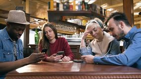 Grupo de amigos elegantes del inconformista que usan el tel?fono elegante durante la reclinaci?n en el pub, barra almacen de video