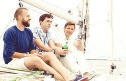 Grupo de amigos em um iate que apreciam um bom dia de verão Férias, feriado, conceito do verão Fotografia de Stock