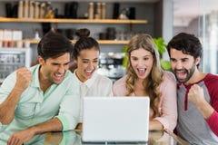 Grupo de amigos emocionados que usan el ordenador portátil Imágenes de archivo libres de regalías