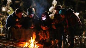 Grupo de amigos en el bosque del invierno que se sienta cerca de la hoguera, escuchando una historia y conseguir asustado metrajes