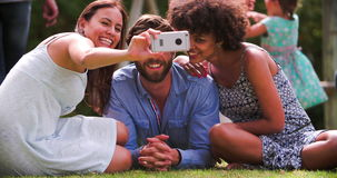 Grupo de amigos en el jardín que toma Selfie en el teléfono móvil almacen de metraje de vídeo