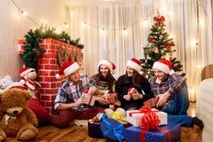 Grupo de amigos en la Navidad, Año Nuevo que se sienta en el ingenio del piso Fotografía de archivo libre de regalías