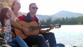 Grupo de amigos en la playa que toca la guitarra en un día de verano al lado del río de la montaña Fotografía de archivo libre de regalías