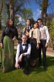 Grupo de amigos en la ropa, la columna y el reloj de sol de Vicorian en el parque Fotografía de archivo
