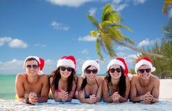 Grupo de amigos en sombreros del ayudante de santa en la playa Foto de archivo libre de regalías