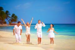 Grupo de amigos entusiasmado felizes que têm o divertimento na praia tropical, férias de verão Imagens de Stock Royalty Free