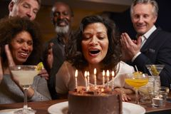 Grupo de amigos envejecidos centro que celebran cumpleaños en barra foto de archivo libre de regalías