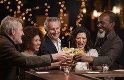 Grupo de amigos envelhecidos meio que comemoram na barra junto fotos de stock
