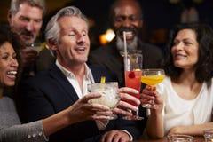 Grupo de amigos envelhecidos meio que comemoram na barra junto foto de stock royalty free