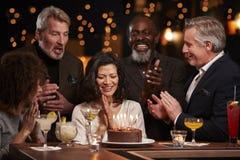 Grupo de amigos envelhecidos meio que comemoram o aniversário na barra foto de stock royalty free
