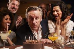 Grupo de amigos envelhecidos meio que comemoram o aniversário na barra fotografia de stock
